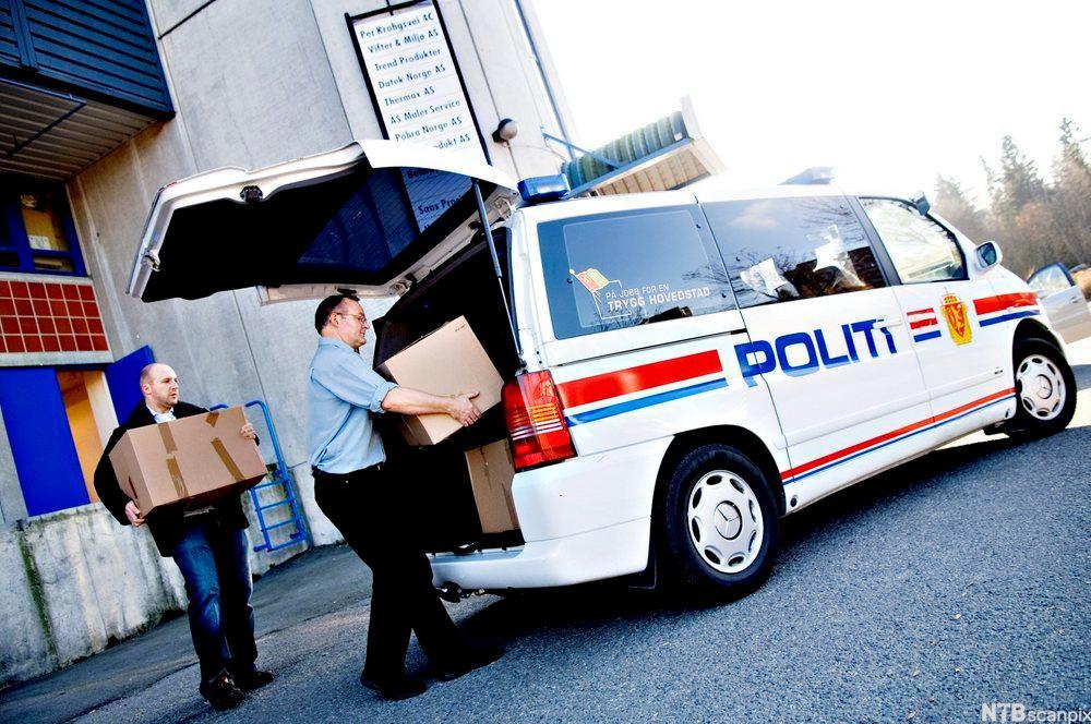 Politibetjenter bærer pappesker og plasserer dem bak i en politibil. Foto