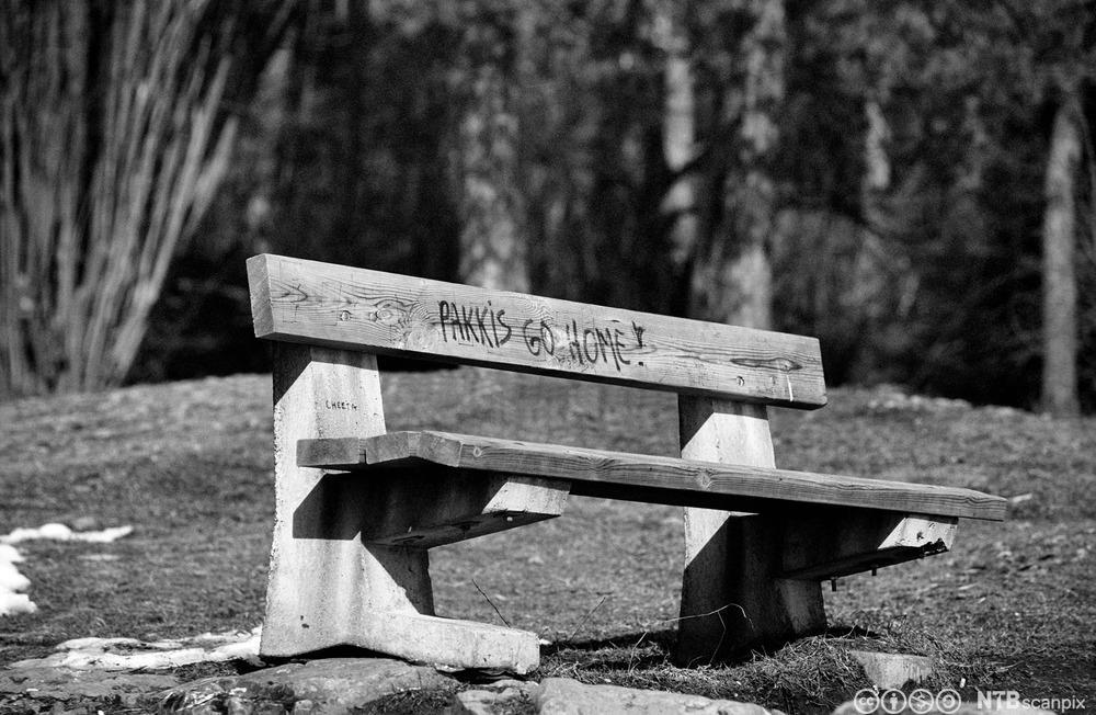 """Bilde av en benk med teksten """"Pakkis go home"""" malt på. Foto."""