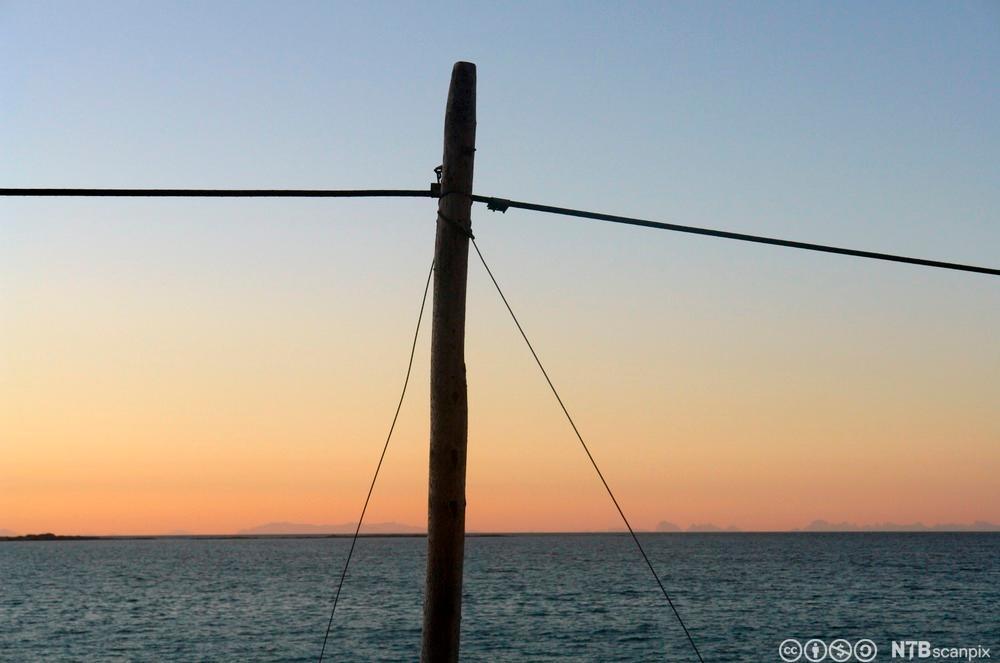 Telefonstolpe med solnedgang over sjøen som bakgrunn. Foto.