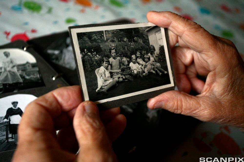 Eldre kvinne holder et gammelt fotografi. Foto.