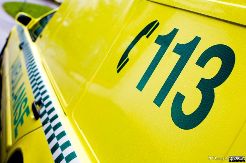 Gul ambulansebil med telefonnr 113 trykket på sideruta bak. Foto.