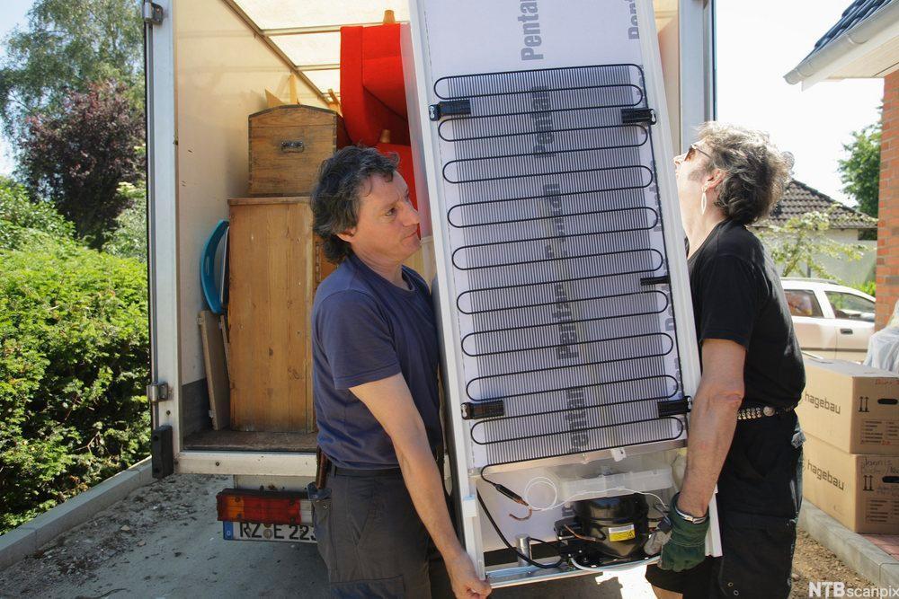 To mennesker som løfter kjøelskap ut av flyttebil. Foto.