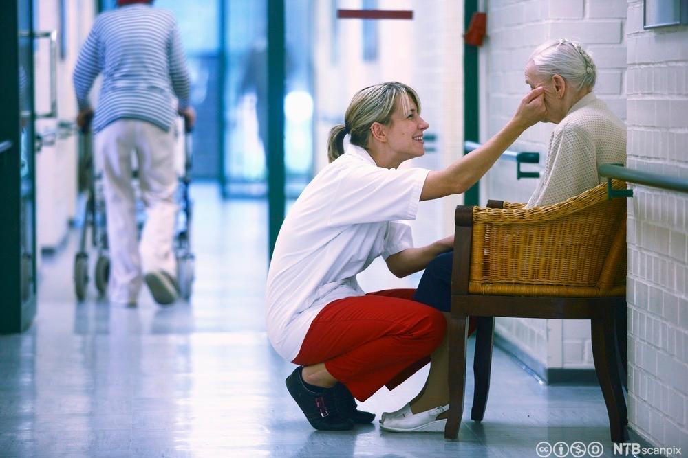 Pleier snakker med beboer og stryker henne på kinnet. Foto.