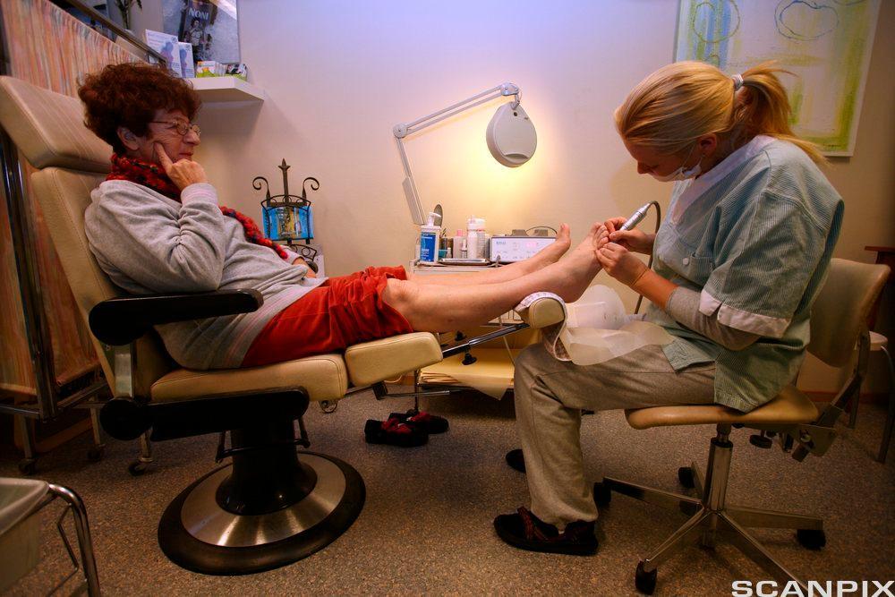 Helsearbeider steller føtter til pasient. foto.