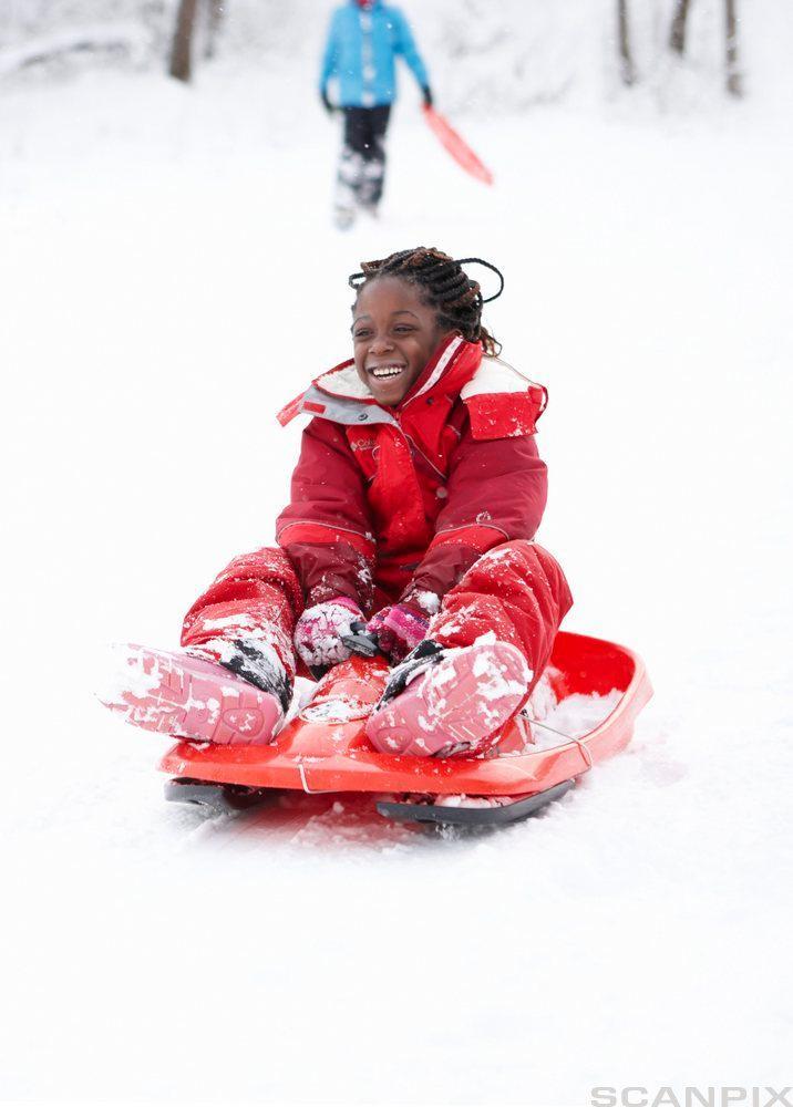 En jente leker i snøen. Foto.