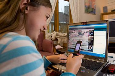 Jente med bærbar pc og mobiltelefon