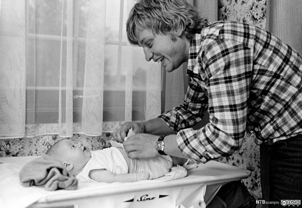 En far som prater med et lite barn som ligger på stellebordet. Foto.