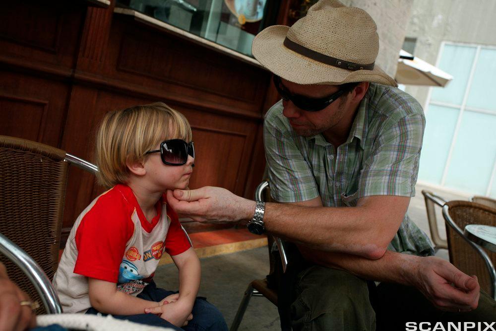 Mann og gutt snakker. Foto.