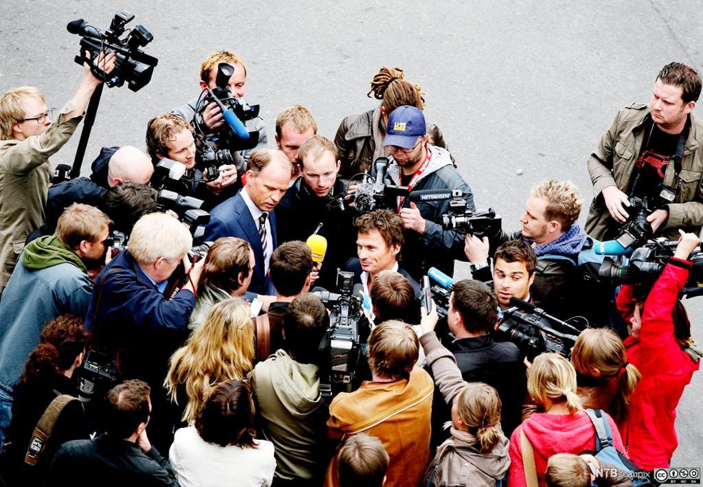 Petter Stordalen omringet av journalister og fotografer. Foto.