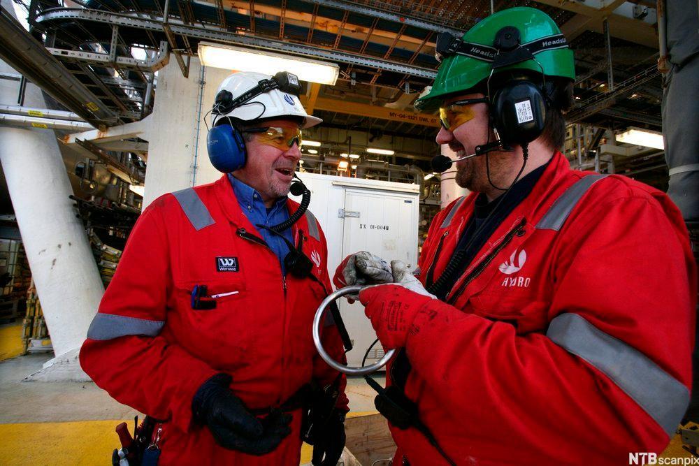 To voksne menn i røde arbeidsdresser, med hjelm og hørselsvern. De står ved siden av hverandre inne i et stort teknisk anleggsbygg og smiler. Foto.