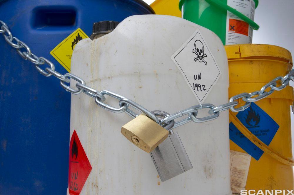 Bøtter og kanner merket med farlig innhold og en kjetting med henglelås rundt. Foto.