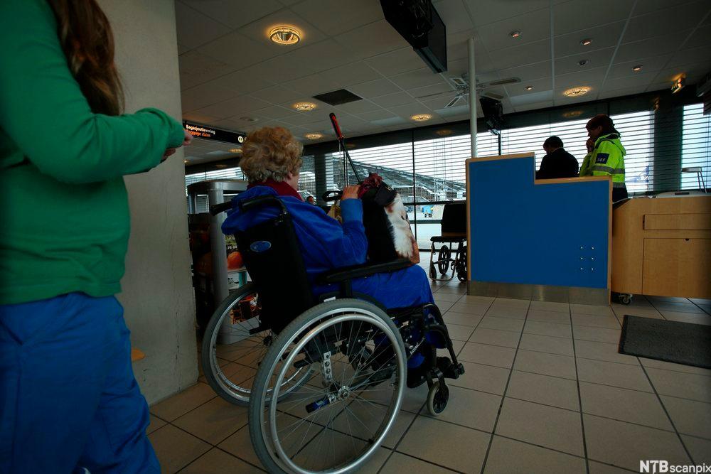 Bevegelseshemmet eldre dame venter på innsjekking på flyplass.Foto.