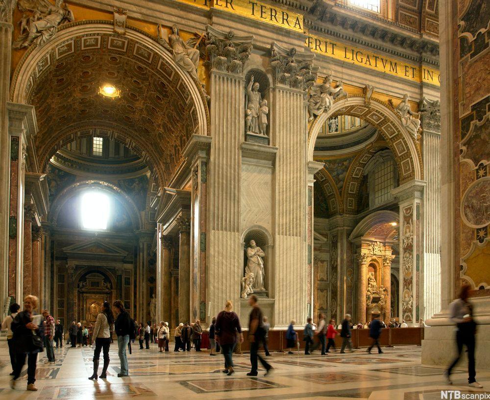 Store boger og barokk utforming inne i eit stort kyrkjerom. Foto.