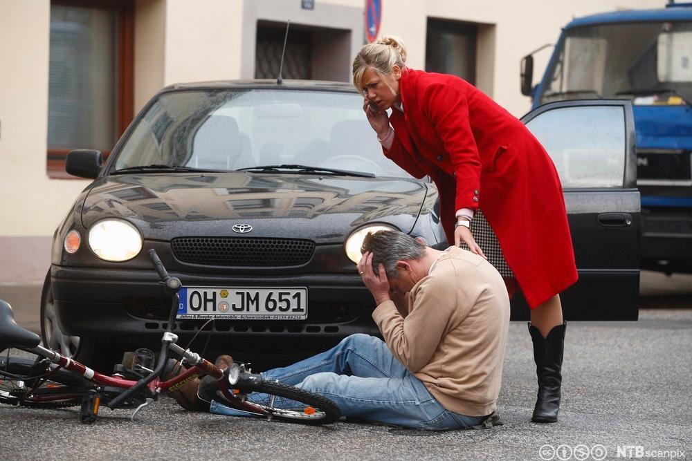 Syklist påkjørt av bil. Kvinne ringer ambulanse.Foto.