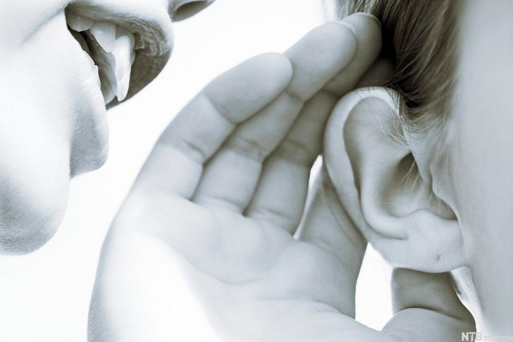 Person snakker mot øret til en annen. foto.