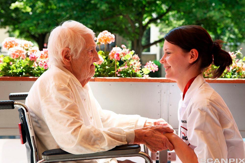 Helsefagarbeider i samtale med eldre mann. Foto.