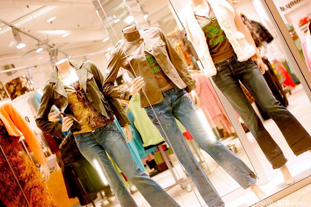 Utstillingsvindu i klesbutikk, med dukker som er kledd i olabukse, t-skjorte og kort jakke. Foto.