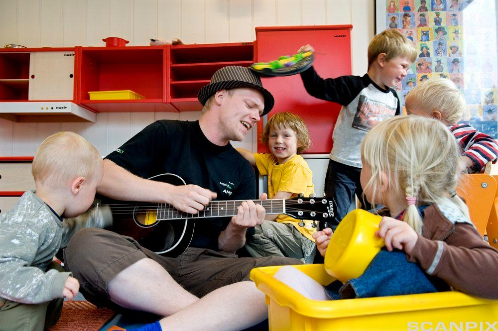 Barnehageansatt spiller synger med barna. Foto.