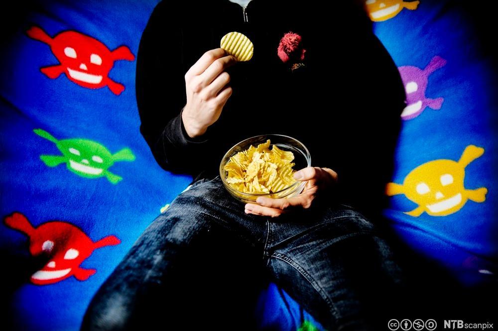 Gutt sitter i sofa og spiser potetgull