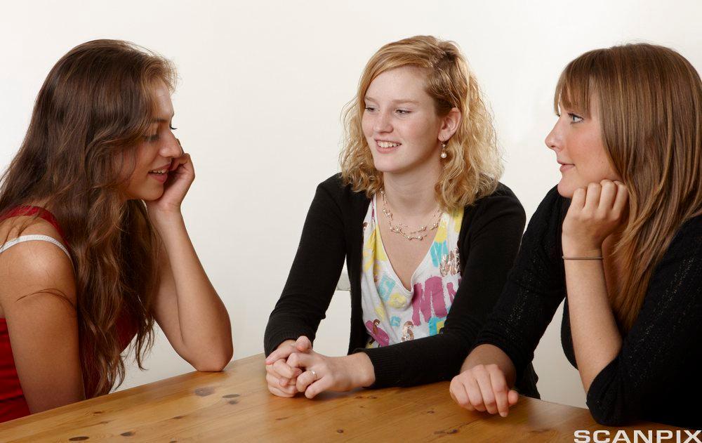 bildet viser tre ungdommer som sitter å snakker sammen