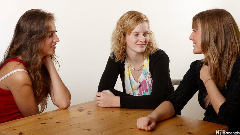 Tre jenter snakker sammen på skolen.