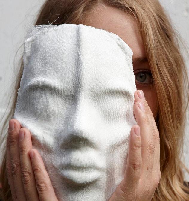 Jente som holder en maske delvis foran ansiktet. Foto.