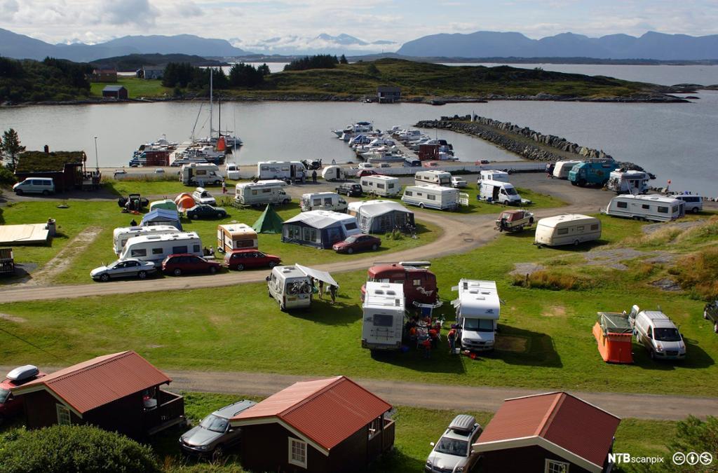 Oversiktsbilde som viser en campingplass med telt, bobiler, utleiehytter og båthavn. Foto.