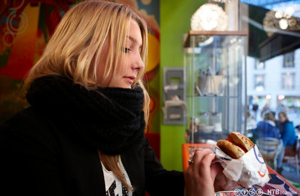En jente på kafe holder noe brødmat i hånden. Foto.