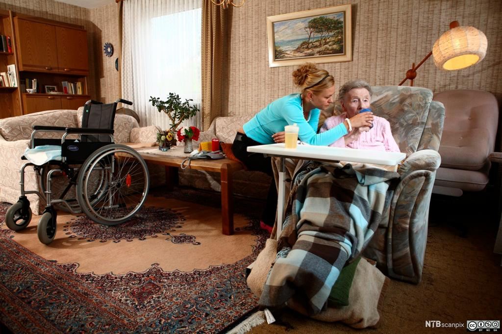 En kvinnelig hjemmehjelp og eldre kvinne. Foto.