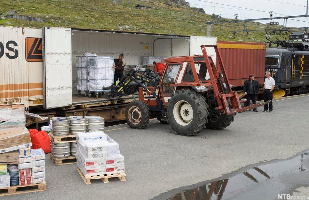 Paller med varer lastes fra lastebil til perrong. foto.