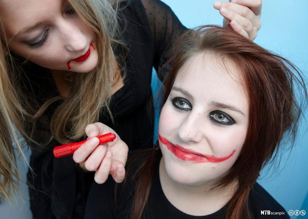 To jenter maler hverandre med ansiktsmaling. Foto.