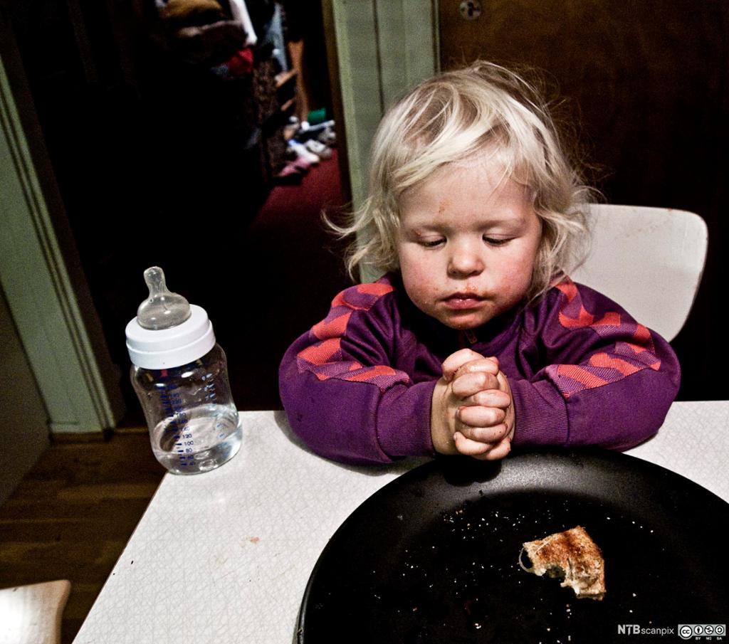 Jente folder hendene ved matbordet. Foto.