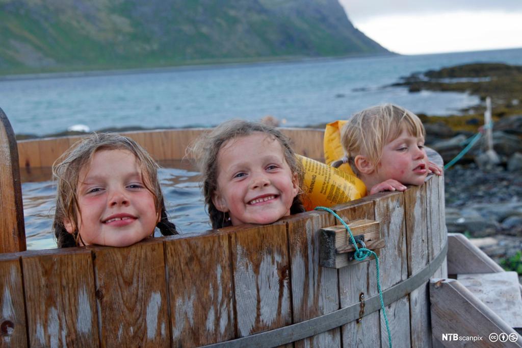 Tre jenter bader i badestamp ut mot havet. Foto.