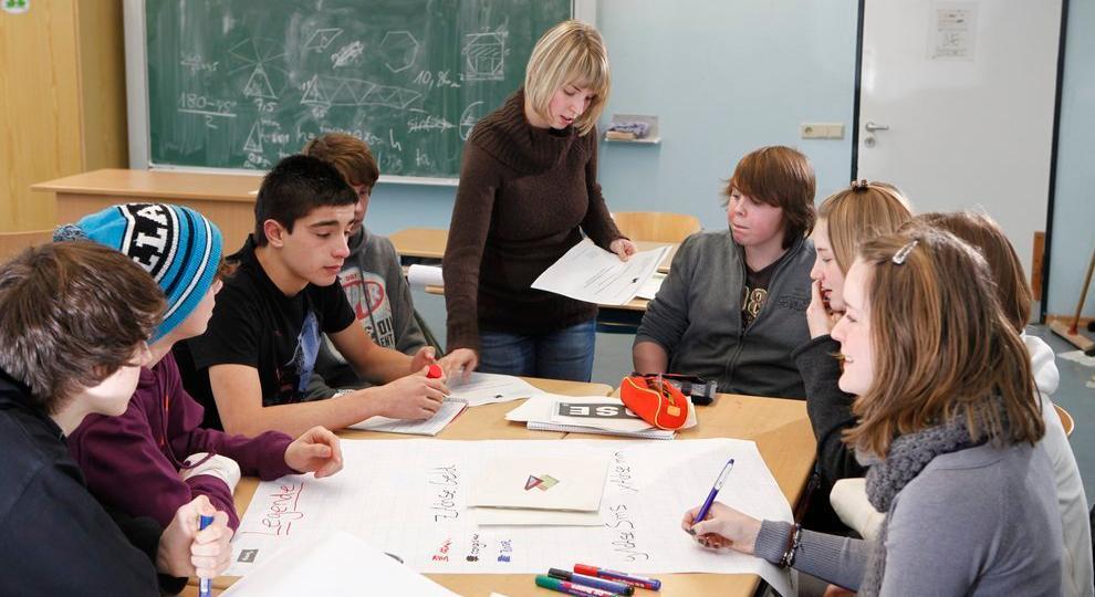 Elever i arbeid rundt et bord. Foto.