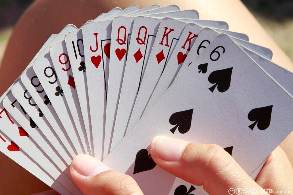 Hand som held spillkort. Foto.