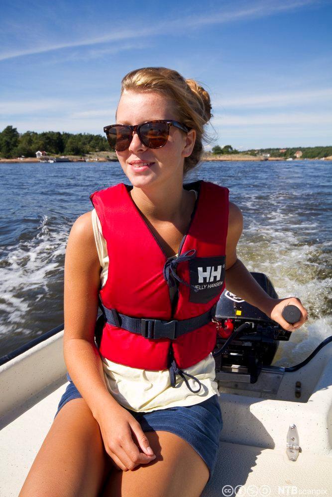 Jente styrer småbåt med påhengsmotor. Foto.