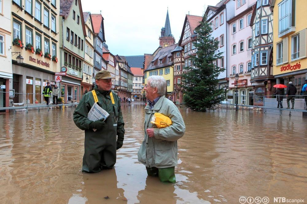En mann og en kvinne står i vann til lårene i en gate. Foto.