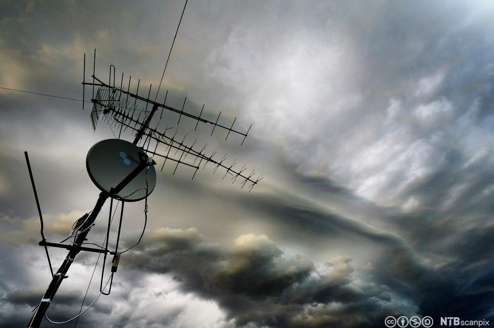 Antenne og parabol på hustak. Foto.