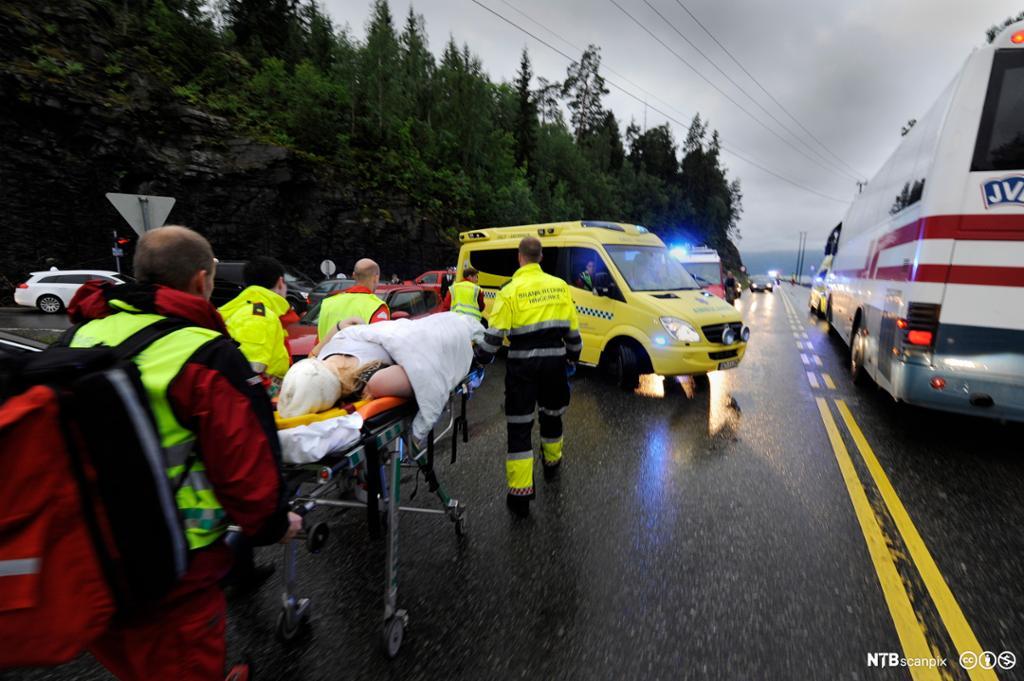 Skadet person fraktes bort på båre av helsepersonell. Foto