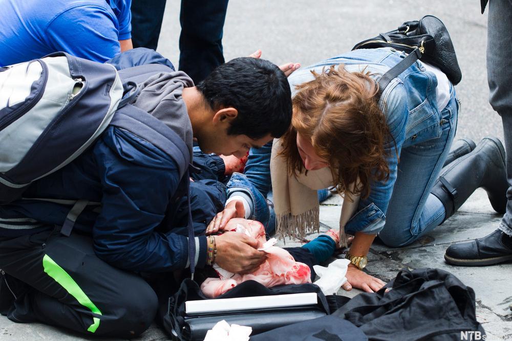 En skadet person på bakken og to som undersøker ham. Foto.