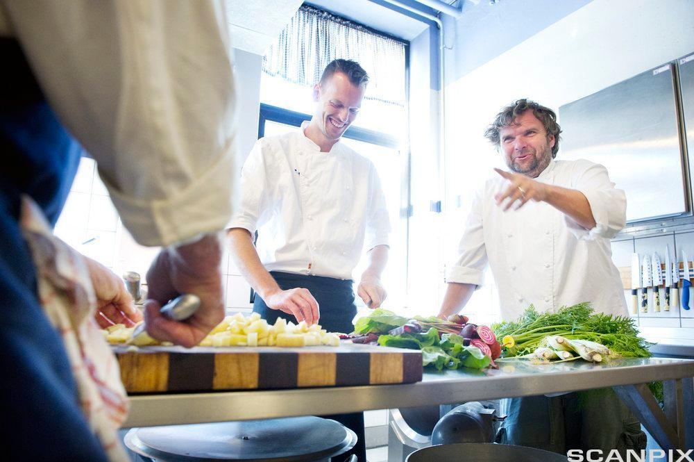 To kokker smiler og har det hyggelig sammen mens de jobber på restaurantkjøkken. Foto.