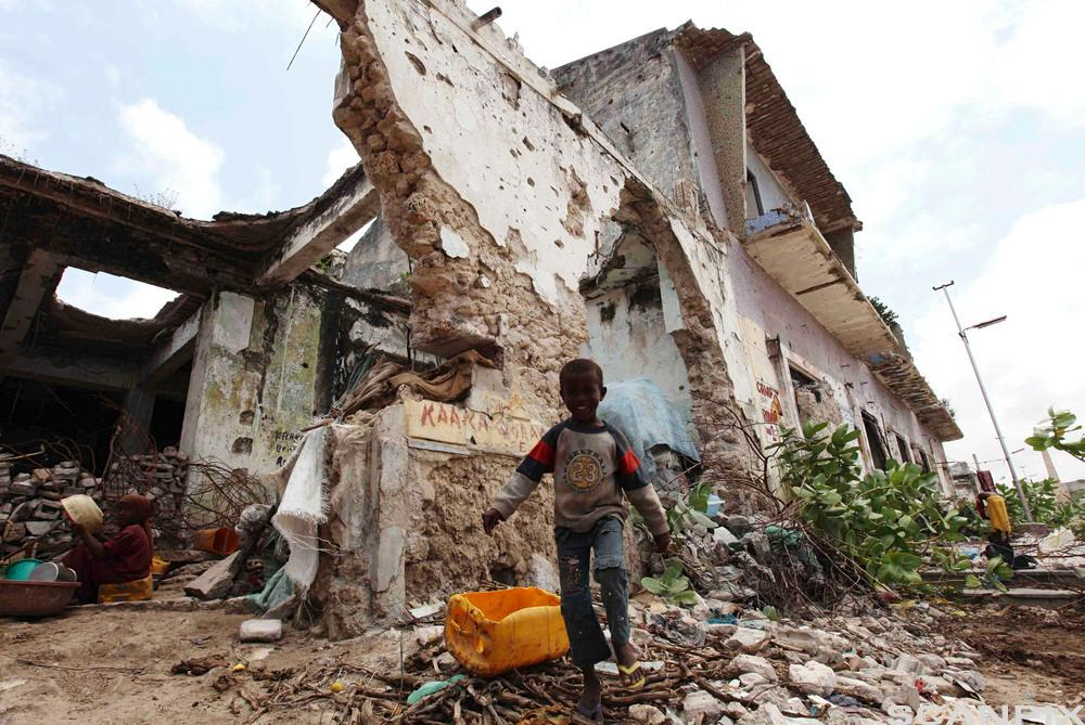 Child plays outside a war-ravaged building in Somalia