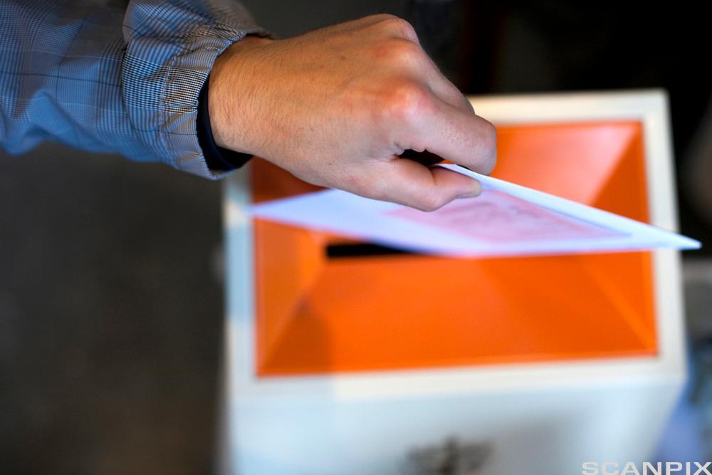 Stemmeseddel puttes i urne. Foto.