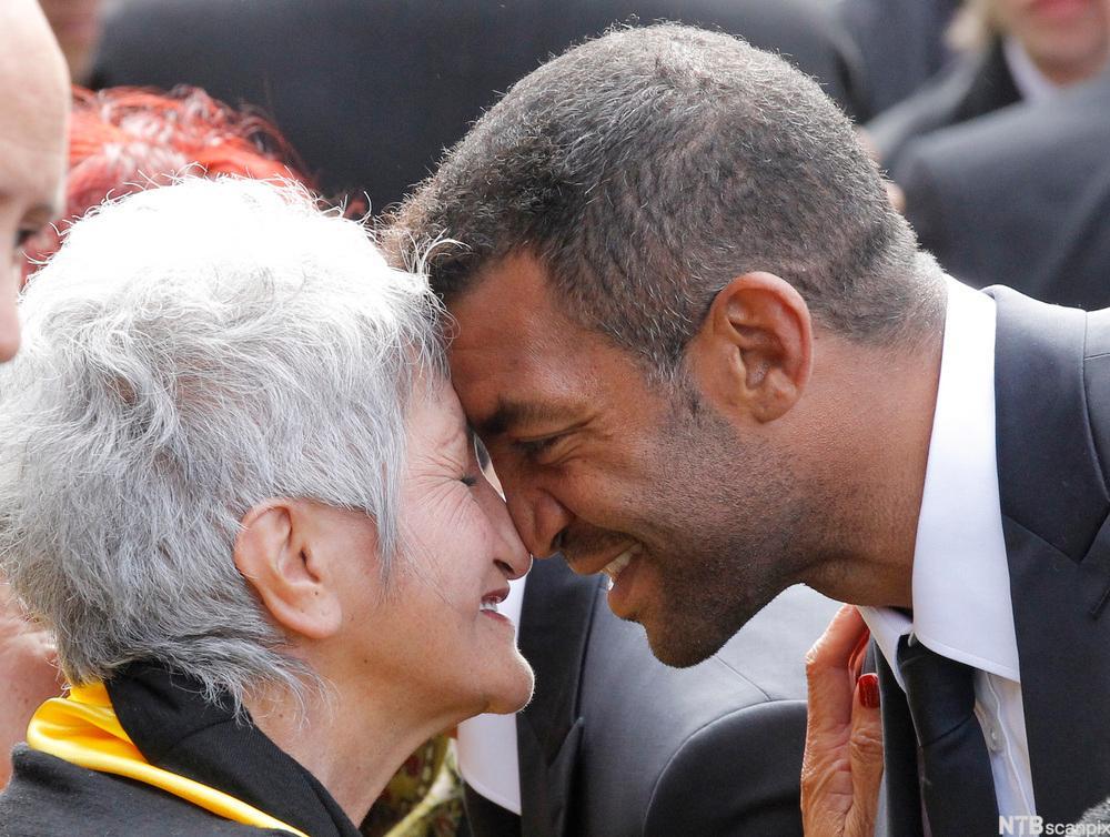 En mann og ei dame hilser nese mot nese. Foto.