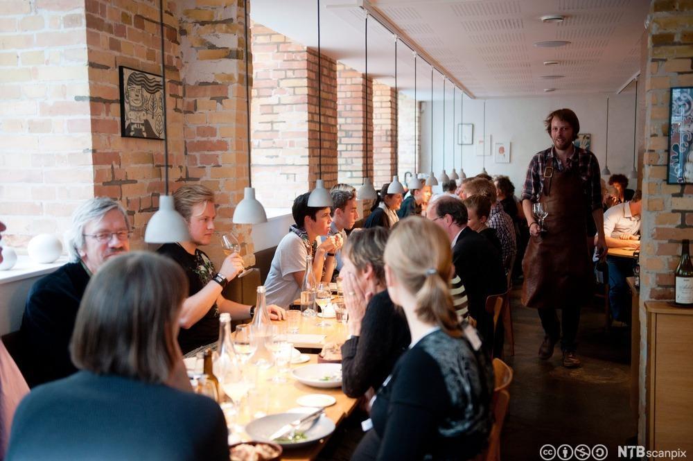 Menneske ved eit langbord på ein restaurant. Foto.