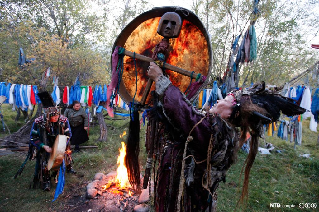 En tuvinsk sjaman fra Sibir holder en tromme over ild. Foto.
