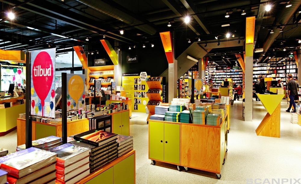 Hyller og bord som presenterer bøker inne i en bokhandel. Foto