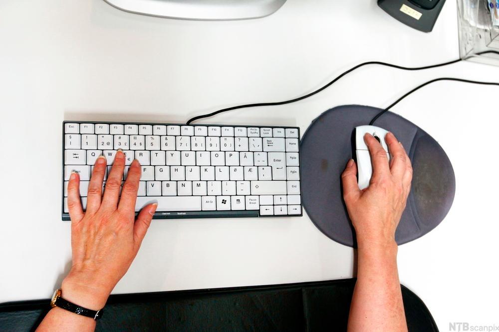 Mann som sitter med lavt tastatur og mus med musmatte foran seg. Foto