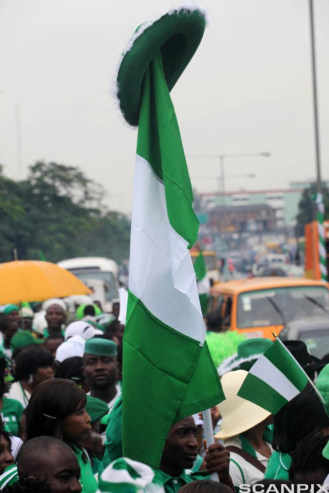 A man raises the Nigerian flag during a street procession marking the 51st independence celebration