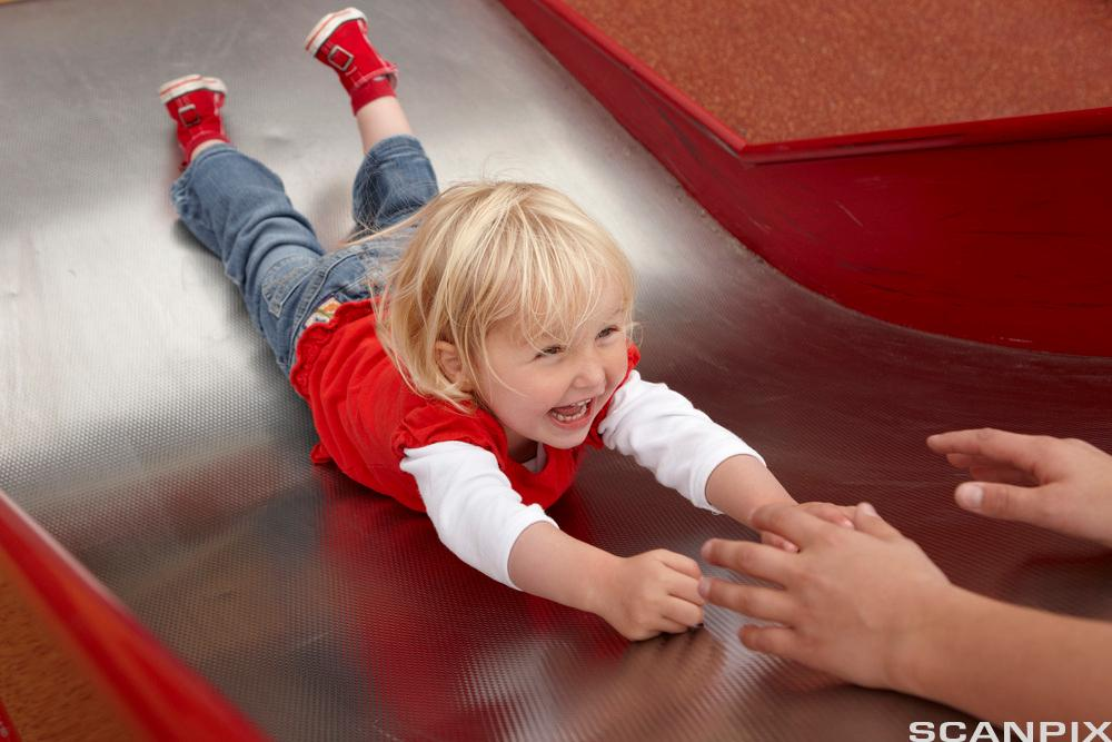 En liten jente sklir ned en rusebane på magen. Foto.